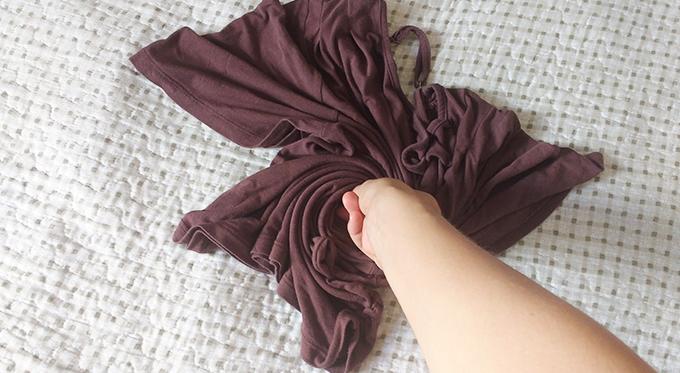 Mão torcendo a blusinha.