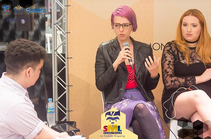 Thiago Galvão olhando para mim, que estou falando no microfone, ao lado, Ma Moraes.