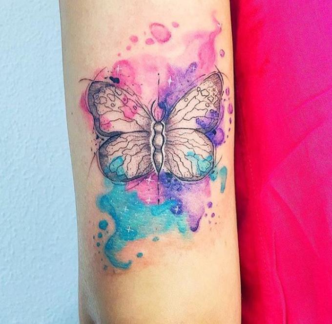 Tatuagem de borboleta com aquarelas rosa, roxa e turquesa, no dia que foi feita