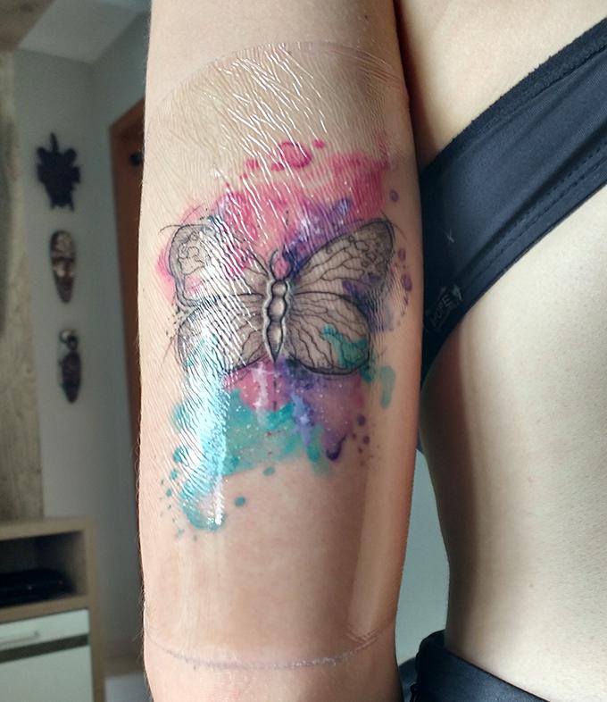 Tatuagem de borboleta com aquarelas, desta vez com o plástico que protege a tatoo.