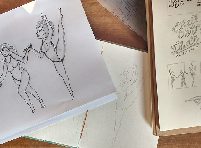 Mesa com os rascunhos do desenho, o caderno com o desenho mais bem elaborado e ele já transpassado para o sketchbook